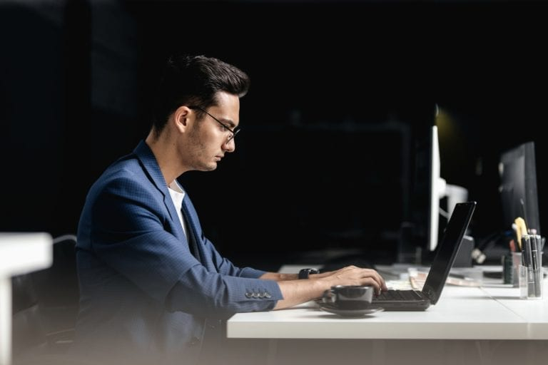 Professional architect dressed in a business suit works on the laptop in the office