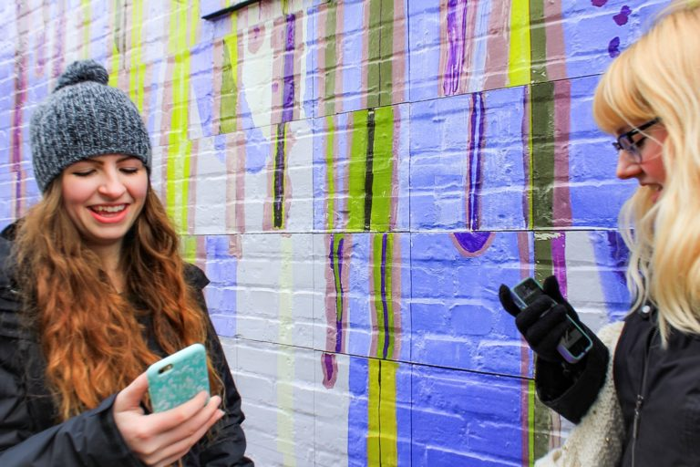 Two young women in winter attire by colorful wall using social media on cell phones taking selfies
